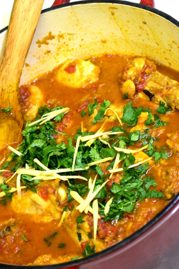 chicken masala in a red dutch oven after adding cilantro and julienne ginger