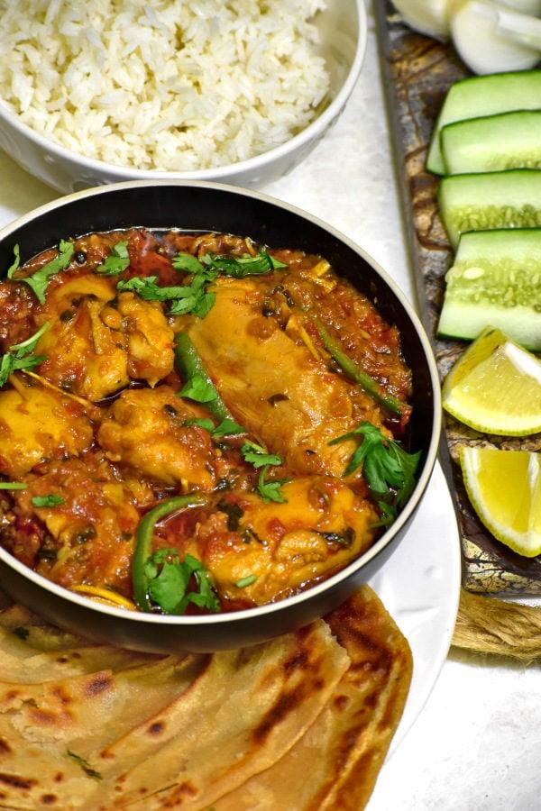bowl of chicken masala alongside rice and roti cut lemons and cucumber
