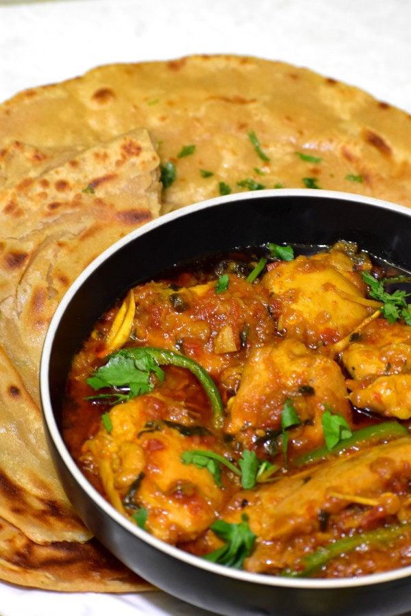 bowl of chicken masala alongside roti