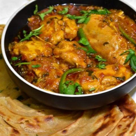 bowl of chicken masala alongside rice and roti