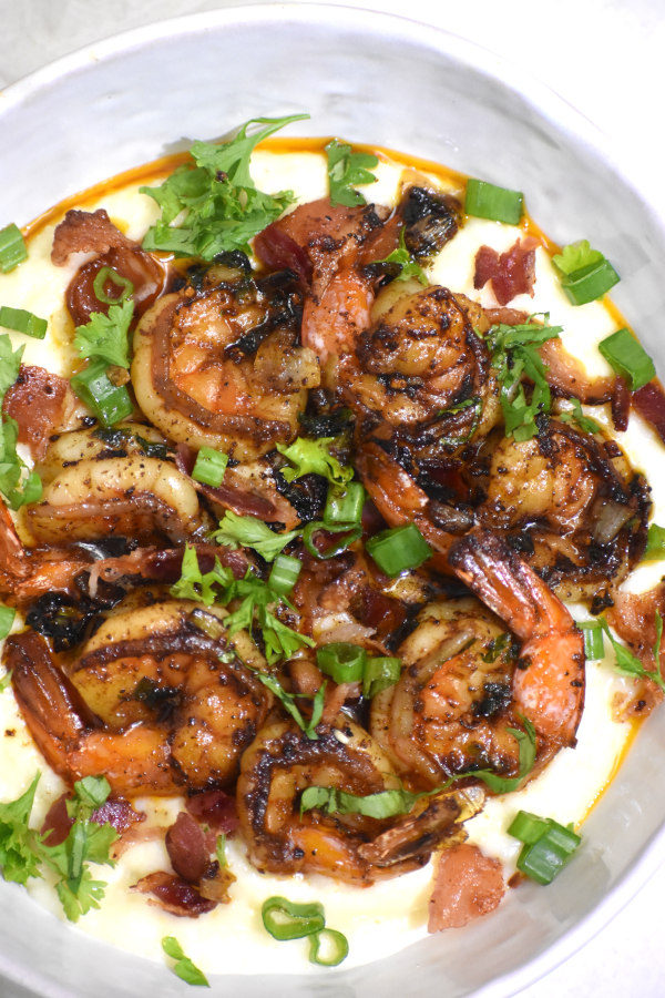 blackened shrimp and grits in a white bowl