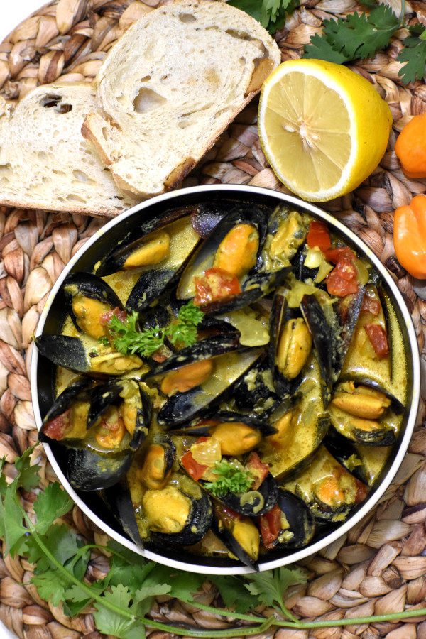 caribbean coconut mussels in a bowl next to slices of bread and a half lemon