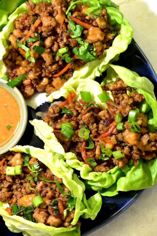 Envueltos de lechuga con pollo en un plato azul junto a salsa de cacahuete