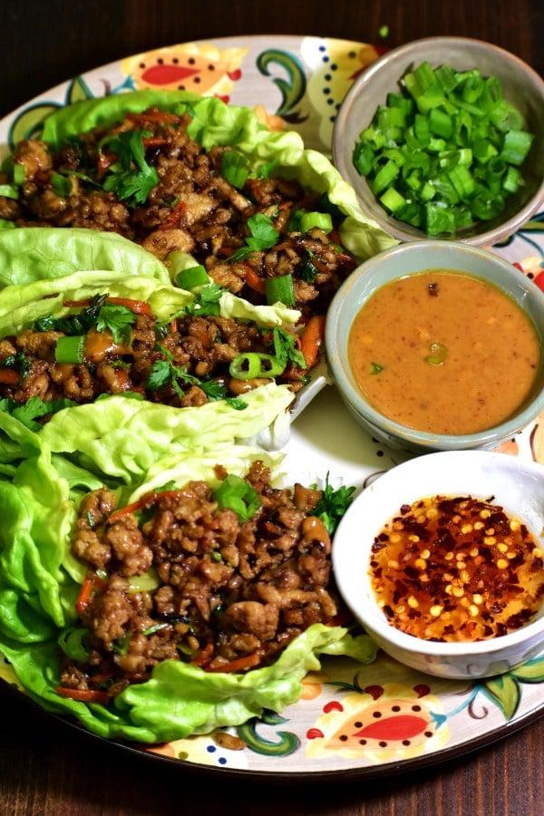 Envoltorios de lechuga de pollo en el plato gitano con salsa de cacahuete, salsa de ajo y chile y cebollas verdes
