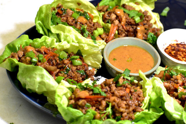 chicken lettuce wraps on a blue platter with peanut sauce on the side