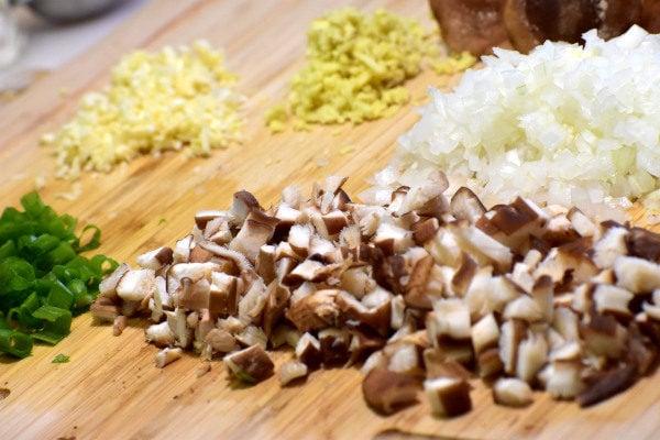 chopped shitake mushrooms, onions, ginger, garlic and green onions on a bamboo cutting board