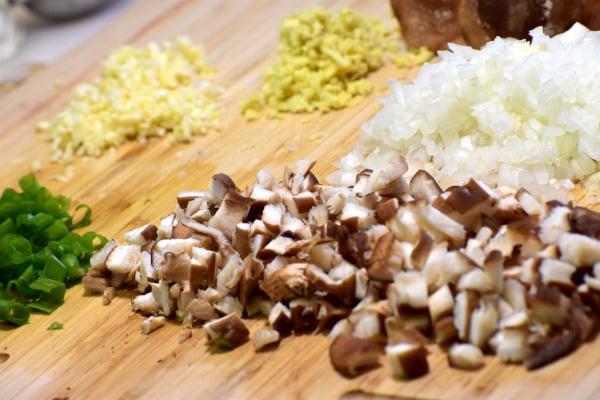 Picar las setas shitake, las cebollas, el jengibre, el ajo y las cebollas de verdeo en una tabla de cortar de bambú
