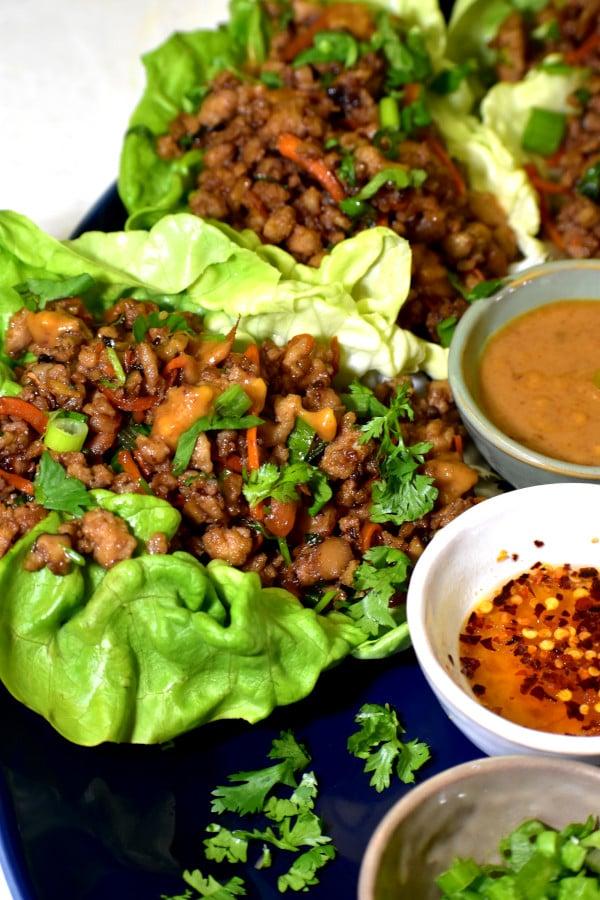 Envoltorios de lechuga de pollo en plato azul con salsa de cacahuete, salsa de ajo y chile y cebollas de verdeo