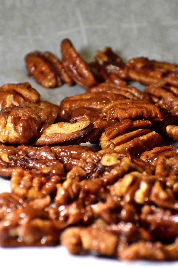 candied pecans on a parchment paper lined baking sheet