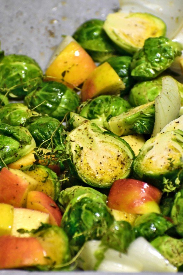 halved brussels sprouts along with chopped onions and apples on a baking tray