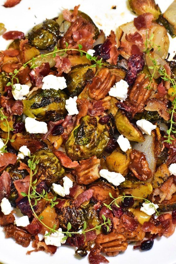 fruity nutty crispy brussels sprouts on a white plate