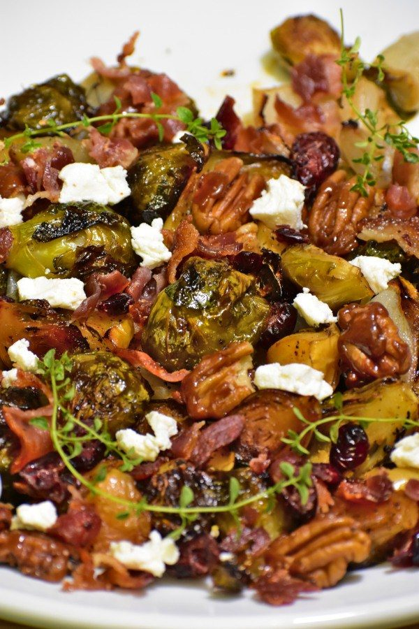 side view of fruity nutty crispy brussels sprouts on a white plate