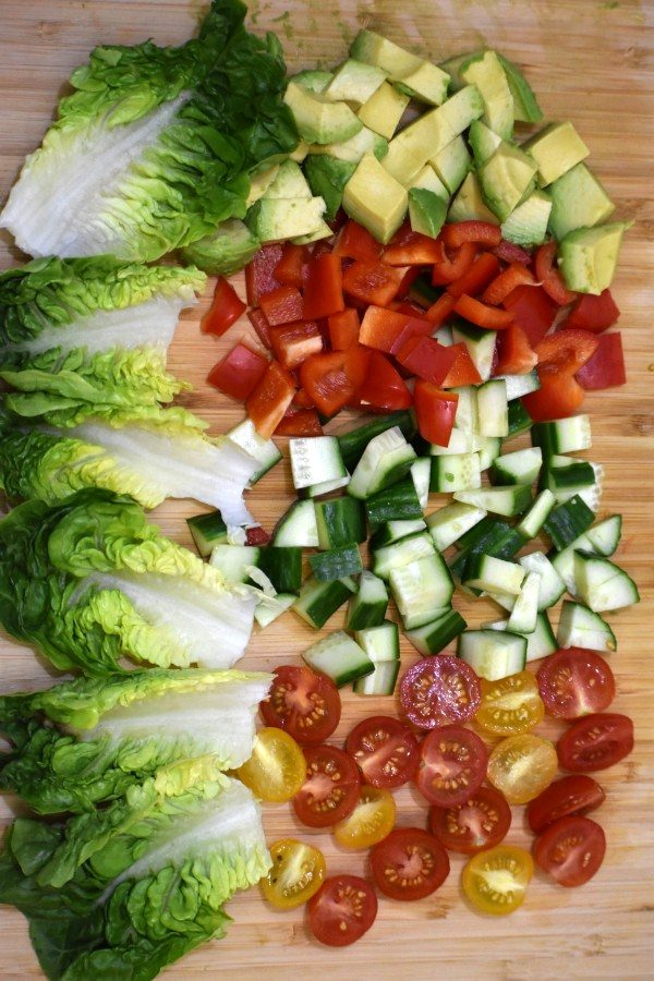 salad leaves alongside chopped avocado, red bell peppers, cucumber and cherry tomatos