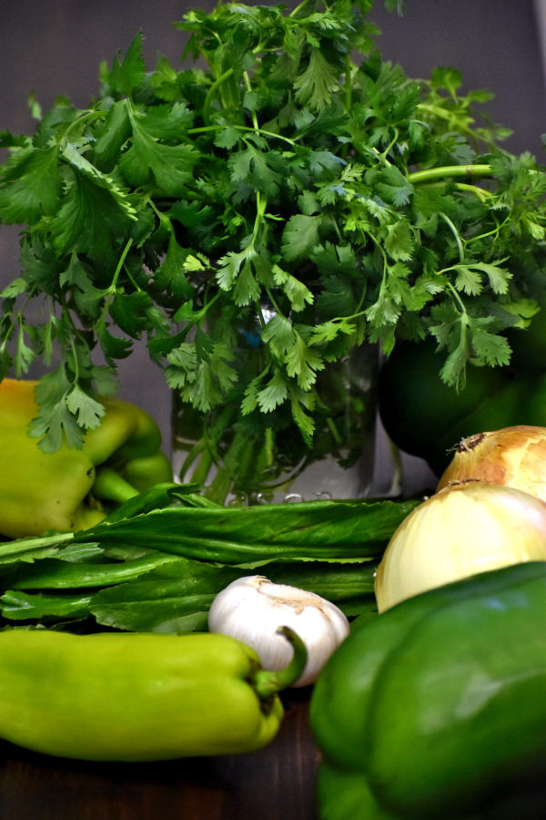 cilantro, onions, garlic, bell peppers and culantro. the ingredients for sofrito.