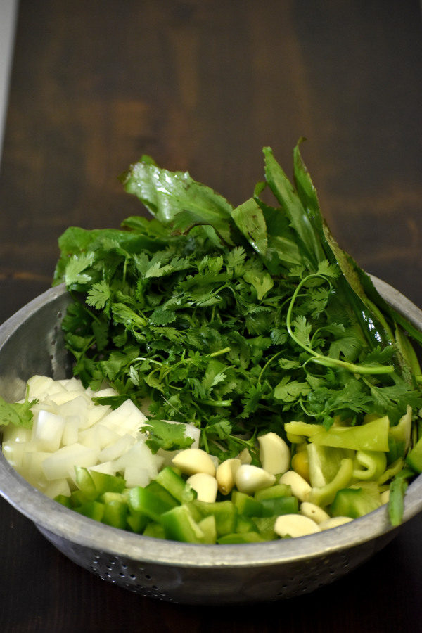 culantro, cilantro, onions, garlic, and bell peppers in a collander