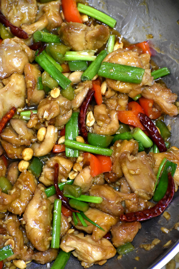 close up of kung pao chicken in a stainless steel wok