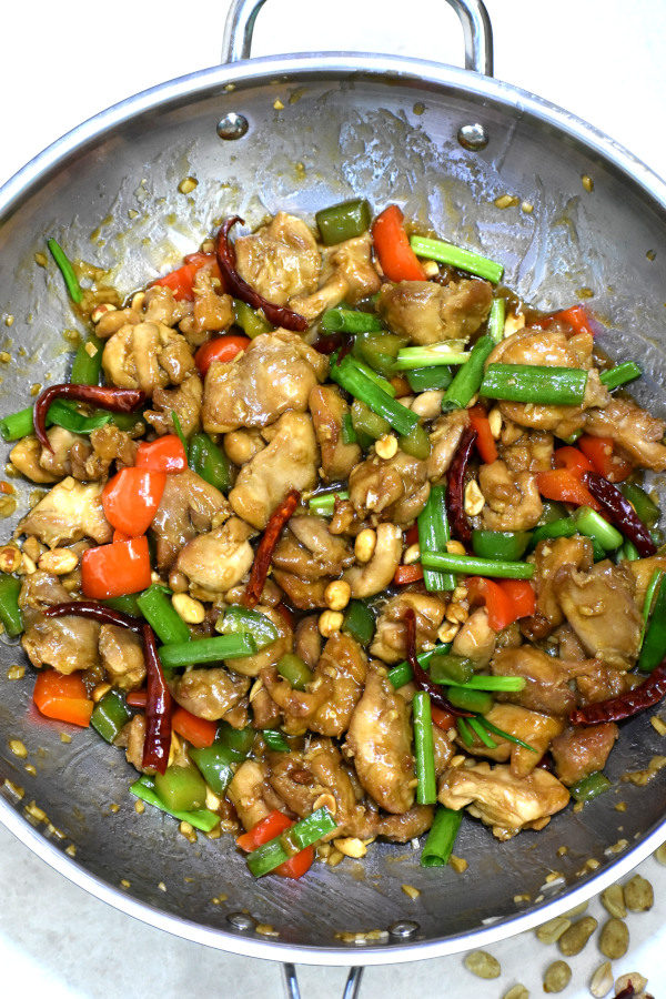 kung pao chicken in a stainless steel wok