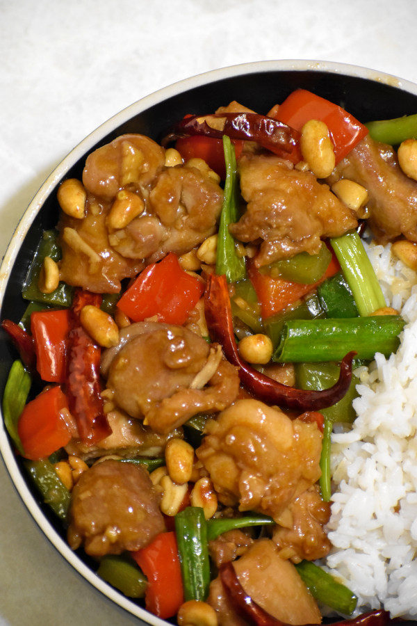 kung pao chicken in a black bowl with rice