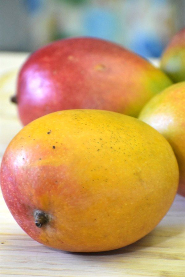 four mangoes on a bamboo cutting board