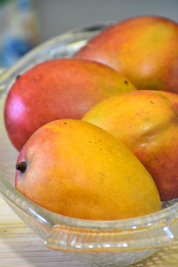 four mangoes in a clear glass bowl