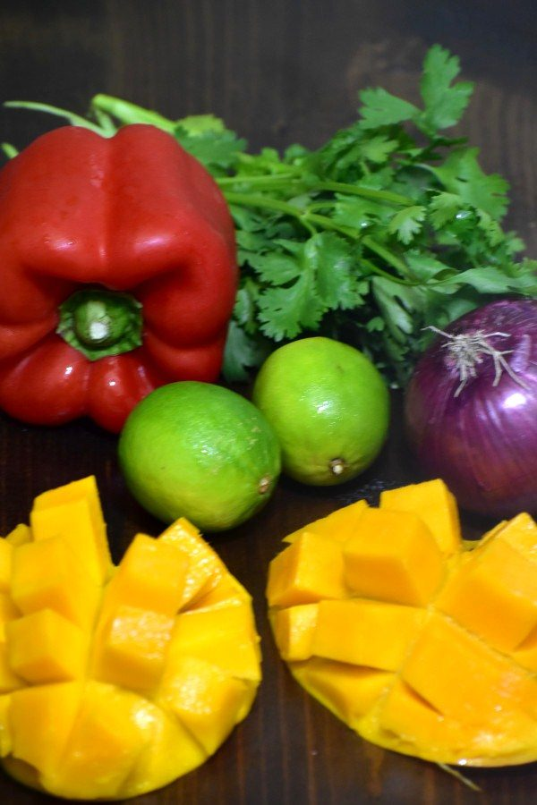 a red bell pepper, red onion, limes, cilantro and artistically cut mangoes on a dark wood background