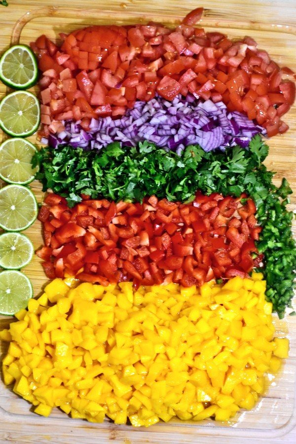 diced mangoes, peppers, cilantro, red onions, tomatoes and limes on a bamboo cutting board