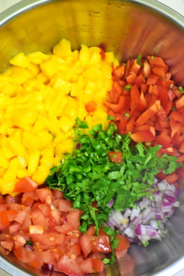 chopped mango, red bell pepper, red onion, tomato and cilantro in a stainless steel bowl