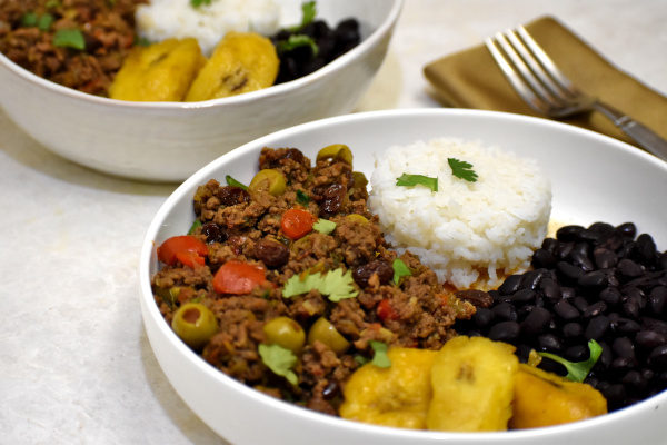 puerto rican picadillo in a white bowl, with another bowl in the background