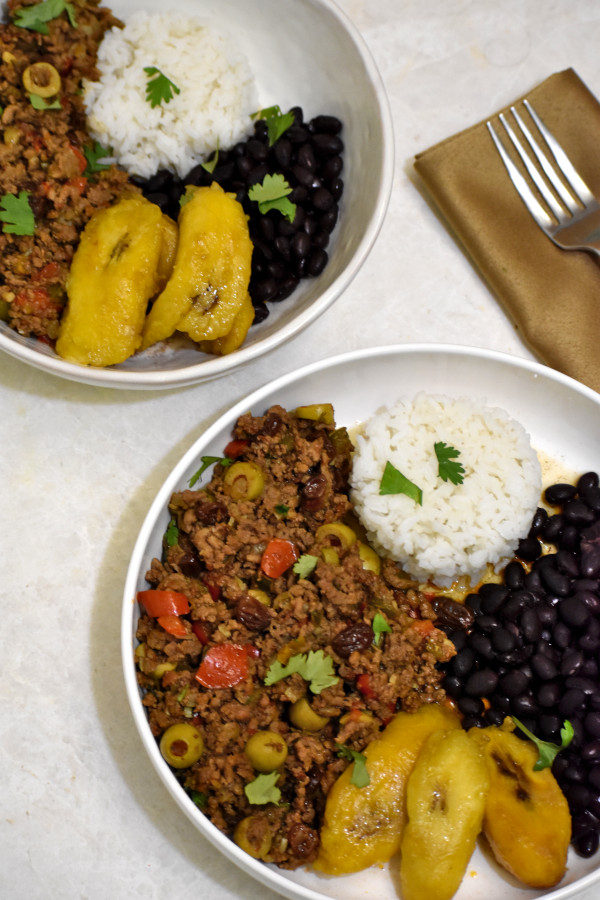 two bowls of puerto rican picadollo with wihte rice, black beans and plantains