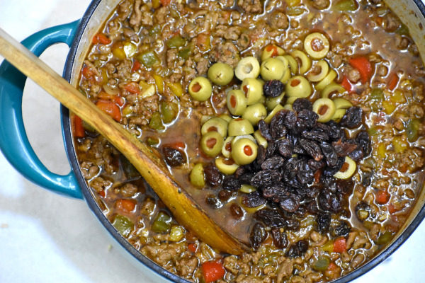ground beef mixture in dutch oven during the preparation of puerto rican picadillo. olives and raisins have just been added.