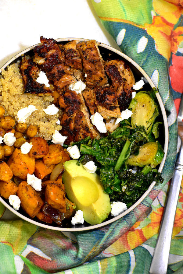 overhead picture of summer detox chicken buddha bowl with colorful napkin beside