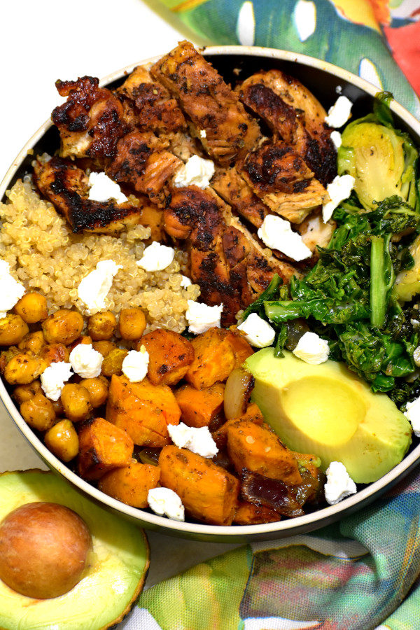 overhead picture of summer detox chicken buddha bowl next to colorful napkin and halved avocado