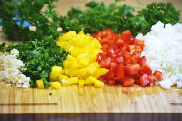 chopped garlic, cilantro, yellow and red bell peppers, onions and parsley on a bamboo cutting board