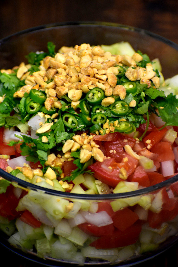 chopped tomatoes, onions and cucumber in a glass bowl topped with cilantro, sliced jalepenos and crushed peanuts