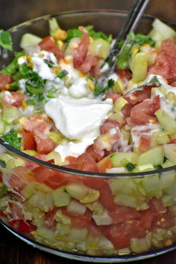 tomato, cucumber and onion in a glass bowl with yogurt added on top