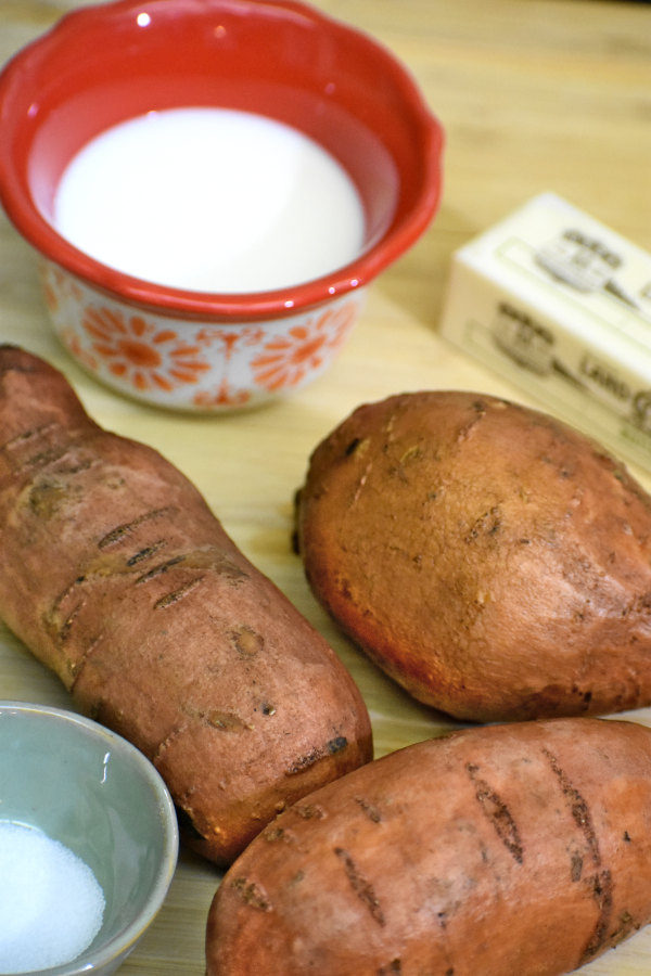 three sweet potatoes, butter, salt and a bowl of milk on a bamboo cutting board