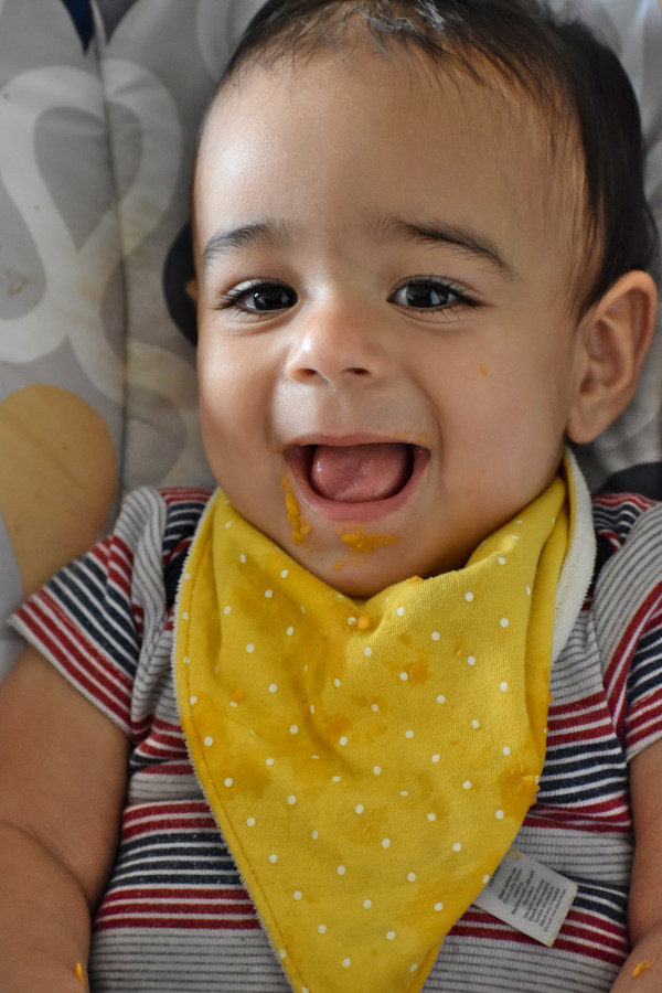 baby noah smiling wearing a yellow bib with mashed sweet potatoes on his chin