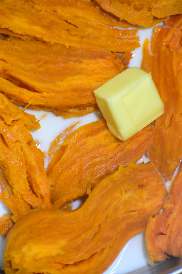 cooked sweet potato flesh in a pan with milk and butter