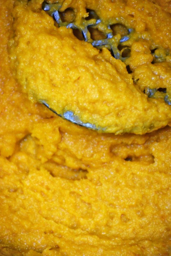 close up picture of mashed sweet potatoes in a pan with the masher