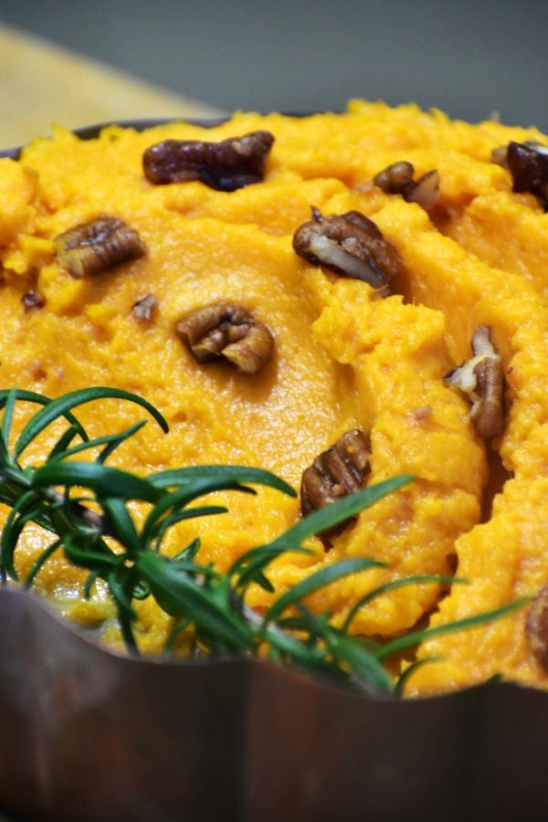 side view of lazy sweet potato mash in a metal bowl with rosemary and chopped pecans
