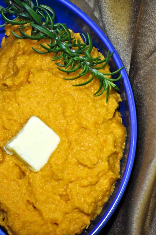 lazy sweet potato mash in a blue bowl with rosemary