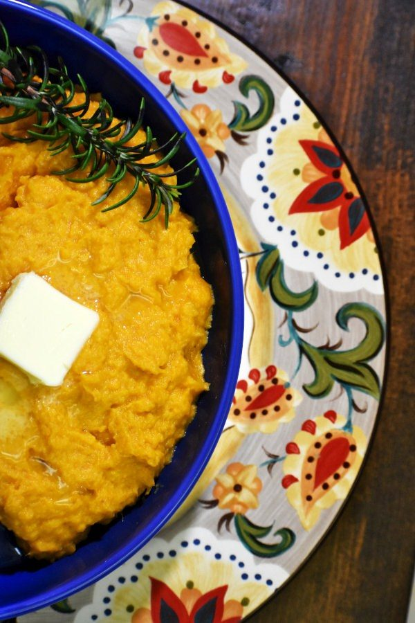 lazy sweet potato mash in a blue bowl on the gypsy plate with rosemary