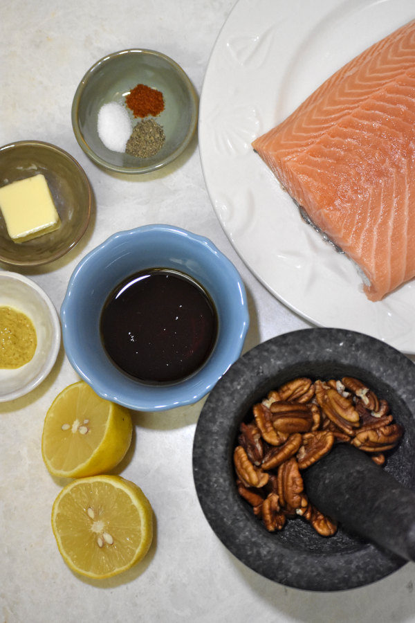 overhead shot of ingredients for maple pecan salmon on a white background