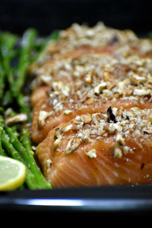 close up view of uncooked salmon glazed with maple sauce and covered with pecans on a black baking sheet, alongside asparagus and lemon slices