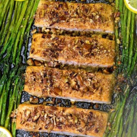 overhead shot of cooked maple pecan salmon on a black baking sheet alongside asparagus and lemon slices