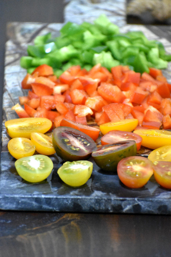 cherry tomatoes and diced red and green bell peppers on a stone cutting board