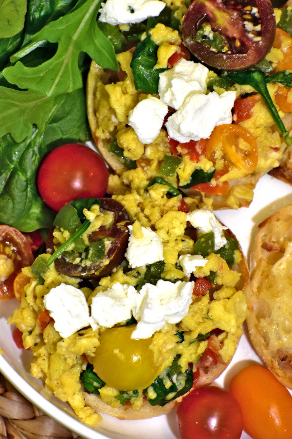 close up of stunning scrambled eggs with english muffins in a white bowl garnished with cherry tomatoes