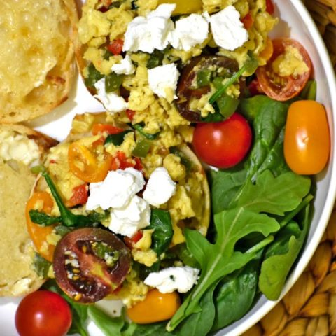 stunning scrambled eggs with english muffins in a white bowl garnished with cherry tomatoes