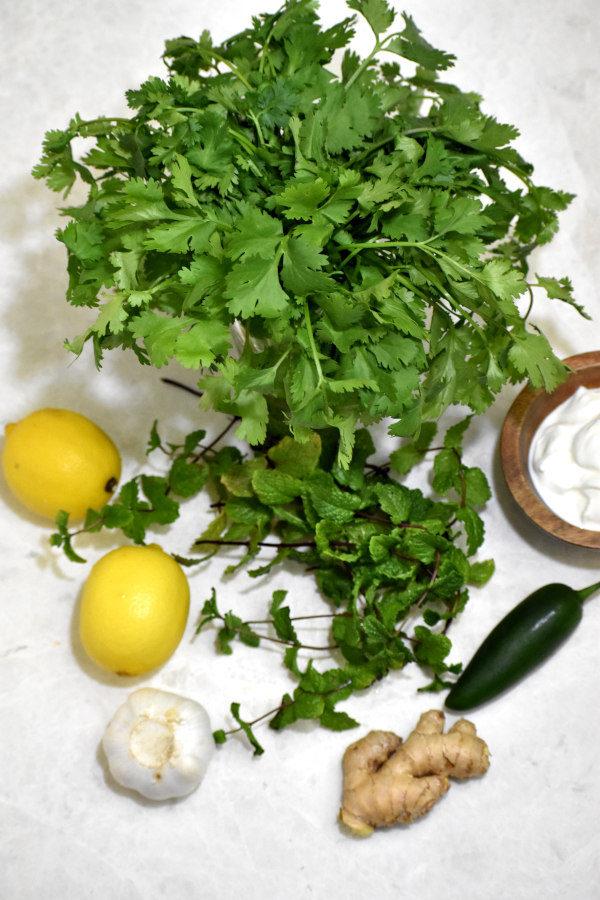 overhead ingredient shot for cilantro mint chutney: cilantro, mint, yogurt, lemons, garlic, ginger and jalepeno