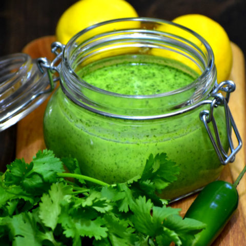 cilantro mint chutney in a glass storage jar with lemons in the background and cilantro and jalepeno in the foreground